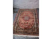 A silk rug, the red field with all over foliate design and blue borders (DELIVERY AVAILABLE)