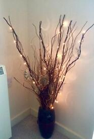 Vase with wooden flowers and lights