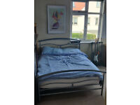 Double bed with silver metal frame and mattress