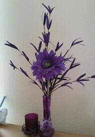 Purple flowers in vase and tealight holder