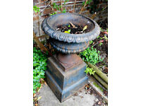 Large, ornate cast iron vintage urn on a rectangular pedestal.