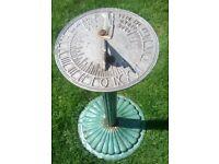 vintage sun dial on green steel pedestal column