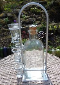 Glass decanter and shot glasses on metal stand.