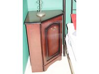 Dark wood corner cabinet with door and shelf