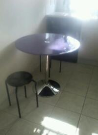 Purple dining table and two black stools