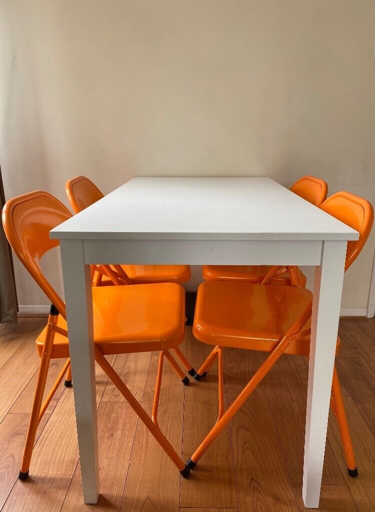 white dining table and folding chairs  in bow london