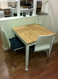 IKEA Lerhamn dining table + 2 white chairs and blue cushions