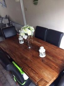 Heavy solid dark oak table and 6 black scroll back leather chairs