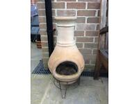 Terracotta chimenea on wire stand