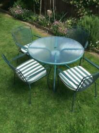 Glass and metal garden table and four metal chairs with cushions