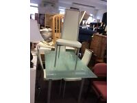 Glass topped dining table plus four white leatherette chairs