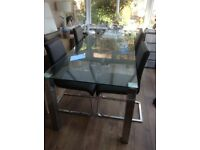 Solid glass clear dining table with four faux leather chairs