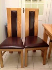 Set of 8 solid oak dining chairs with brown leather seats.