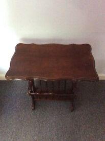 Small dark wood table with magazine rack beneath