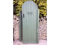 Wooden garden gate, tall with curved top.