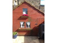 Beautiful wooden playhouse , upstairs and down Just had a new felt roof