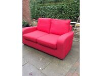 Red two seater sofa. Linen material.