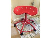 Adjustable, red tractor stool on castors