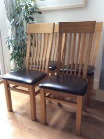 4 high back oak dining chairs with black leather like comfortable seating. Very good condition.
