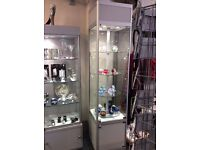 Tall glass display cabinet with revolving display shelves