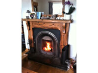 pine mantle with cast iron fireplace and black stone hearth