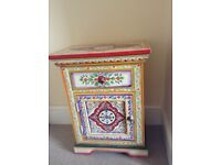 Bedside table, with draw and cupboard. Decorated by hand in lots of bright colours.