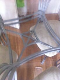 Clear glass dining table with 4 chairs with metal base