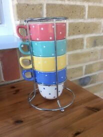 Four mugs in chrome stand, M&S