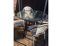 Round glass topped patio table and 4 chairs.
