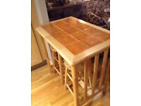 Pine table with orange tiled top and 2 pine stools.