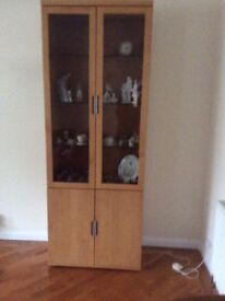 Beech Cupboard with two glass doors at the top and doors opening to shelves at the bottom