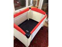 Travel cot as new. 2 heights, changing tray, handy pockets,hood with hanging toys. Carry bag.