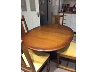 Dark Oak Oval Extending Dining Table and Four Matching Chairs.