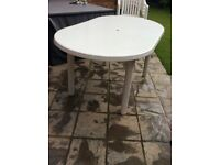 White oval patio table and four chairs