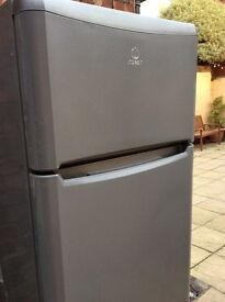 Large High Indesit fridge with small freezer above, grey colour.
