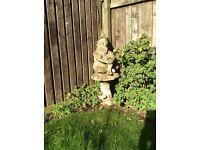 Stone garden gnome sitting on toadstool