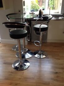 Glass top bar table with 3 chrome and leather gas lift stools.