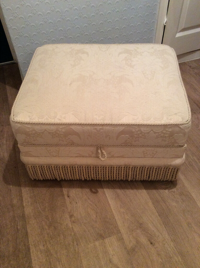 """TOP QUALITY LARGE POUF/FOOTSTOOL WITH STORAGE AS NEWCOST ME195in Stratford upon Avon, WarwickshireGumtree - TOP QUALITY FABRIC CREAM WITH FRINGES BRAIDING AT THE TOP OF THE SEAT, AND FANCY BRAIDING ABOVE THE FRINGES. 25"""" X 20"""" X 15"""". I PAID £195 AND IS STILL AS NEW"""