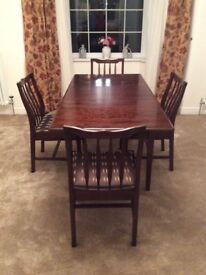 Stag Minstrel extendable dining table with four chairs, dark wood will seat up to six people