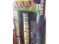 Casio keyboard with stand and music.