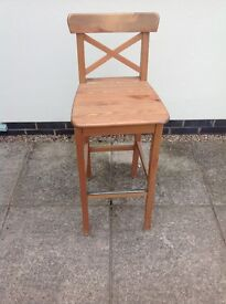4 wooden kitchen stools with seat pads.