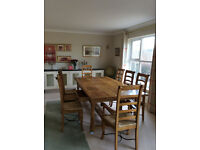 Long, rectangular dining table with 8 chairs, excellent condition.
