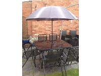 Black glass Garden Table, 6 folding chairs and parasol