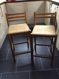 Two kitchen stools. Wooden frames with woven seats.