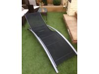 A sun lounger metal frames with mesh seating