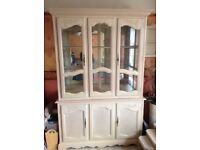 Glass display cabinet. Half glass with shelves and lights and half storage. Cream in colour