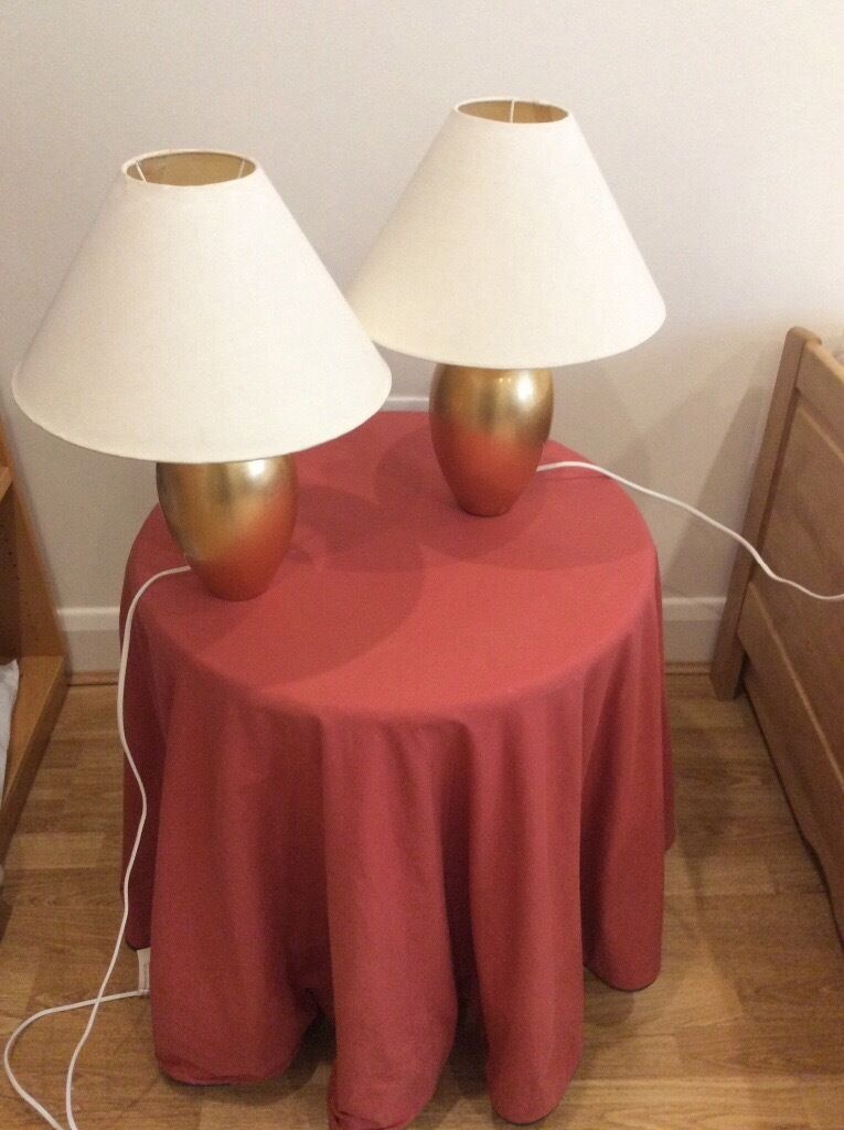 Pair of gold ceramic based table lamps with cream coolie shades
