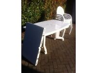 White patio table with six chairs. Large extendable table, dismatles for transport
