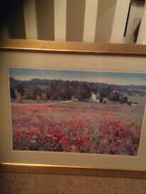 Framed picture. The frame is gold. The picture is country scene.