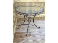 Wrought iron and glass top table with two chairs